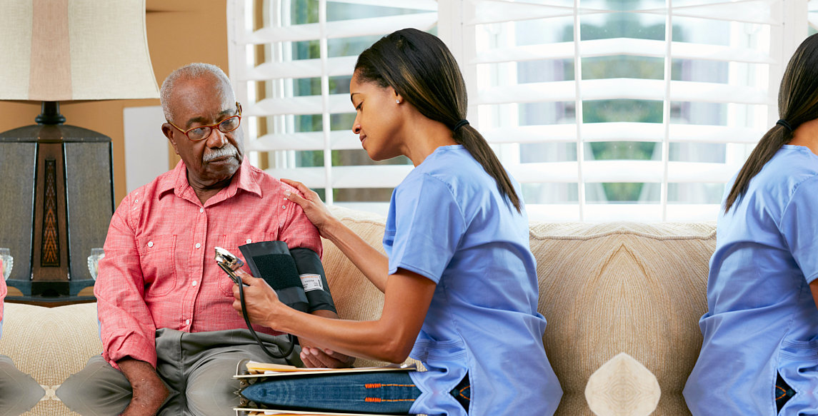 caregiver taking the blood pressure of patient